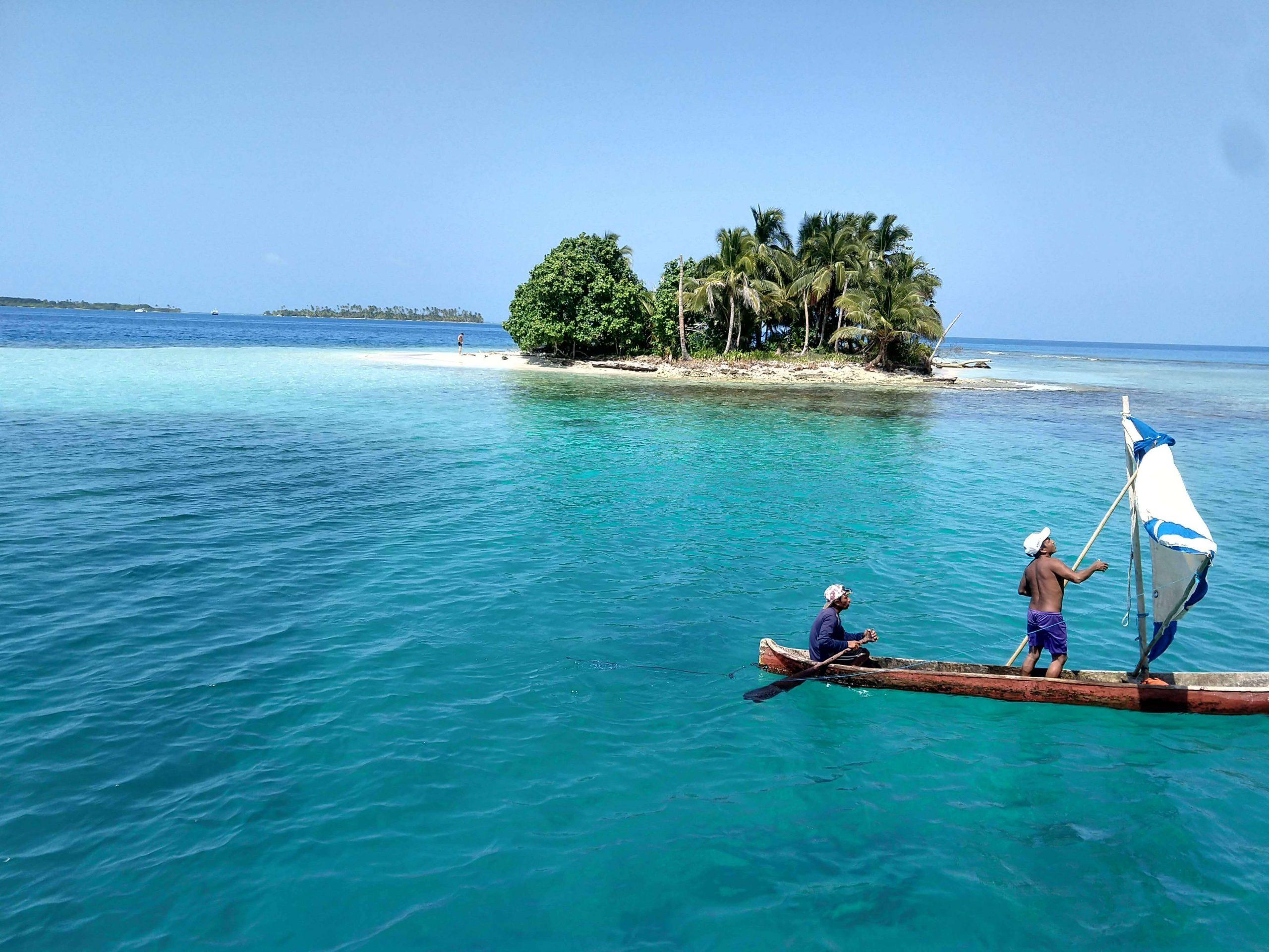San Blas island and traditional Kuna dugout canoe with two local fishermen