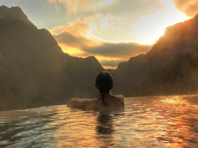 Woman in infinity pool at sunset in Mexico looking at mountains
